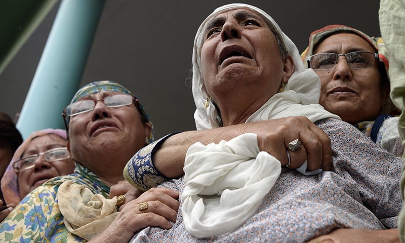 Shujaat Bukhari's mother (C) mourns during his funeral procession. — AFP