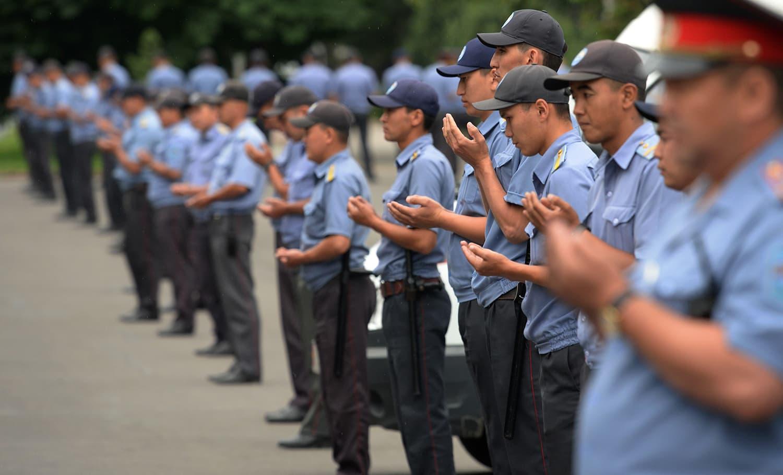 Kyrgyz police officers pray in the centre of Bishkek during celebrations of Eid. — AFP
