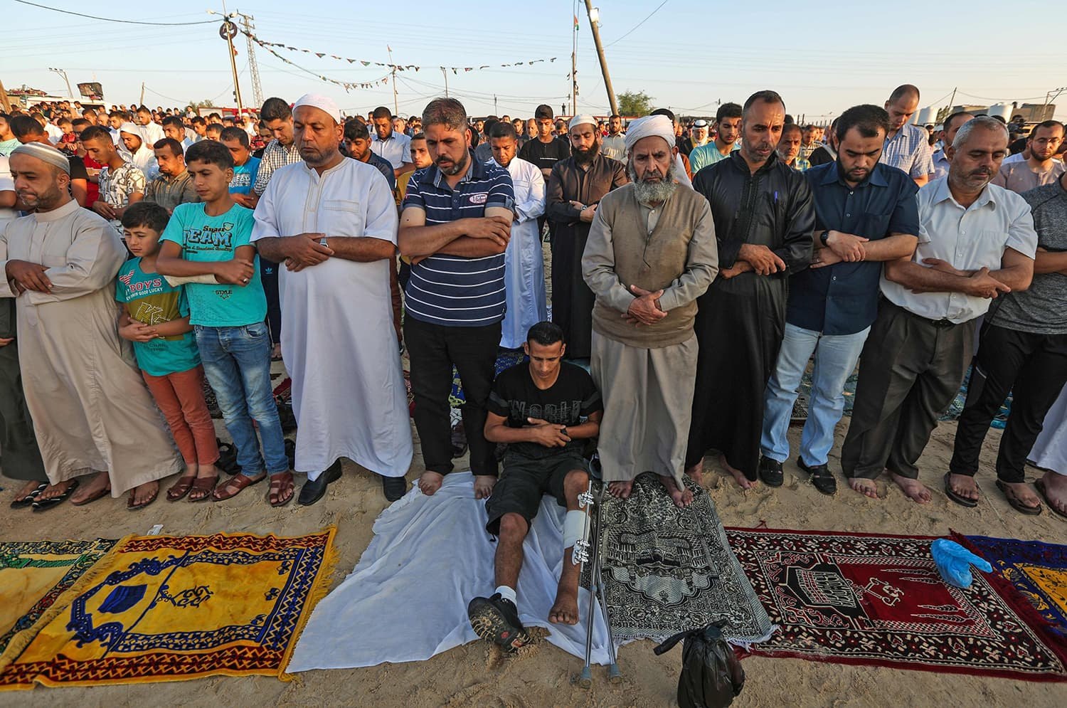 """A Palestinian faithful injured during the """"Great March of Return"""" attend morning prayers during the first day of the celebrations of Eidul Fitr, at the Israel-Gaza border east of Gaza city. — AFP"""