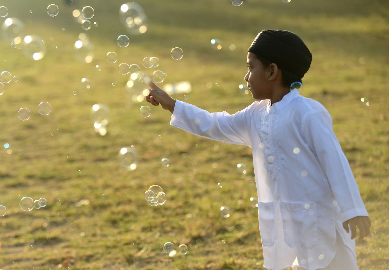 A young boy plays with bubbles as Muslims take part in a special morning prayer celebrating Eidul Fitr festival at Bali's Bajra Sandhi monument and park in Denpasar. — AFP