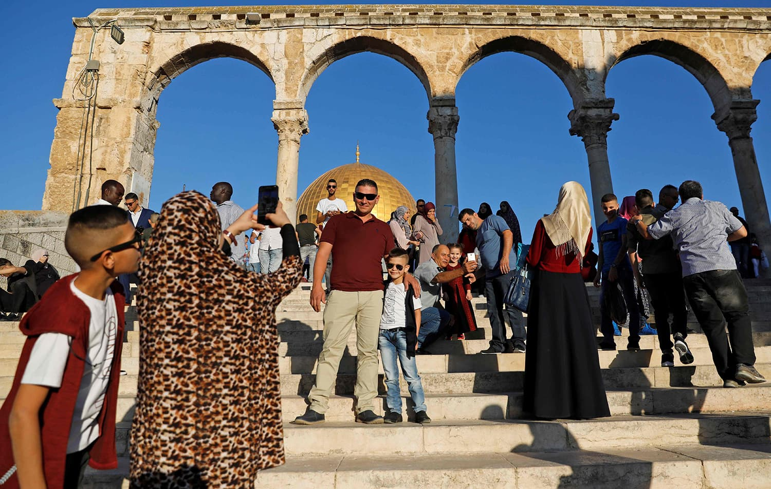 Palestinian Muslims take pictures as they gather for the morning Eid prayer near the Dome of Rock at the Al-Aqsa Mosque compound. — AFP
