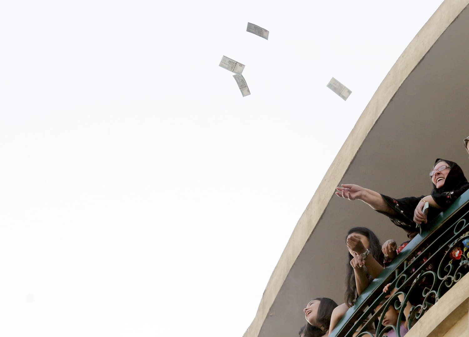 People throw money from a balcony as gifts to passing Muslims celebrating Eidul Fitr outside al-Seddik mosque in Cairo, Egypt. — AP