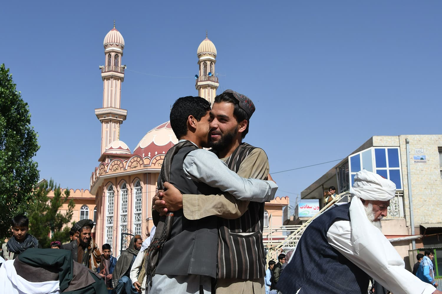 Afghan residents greet each other after Eid prayers in Ghani. — AFP