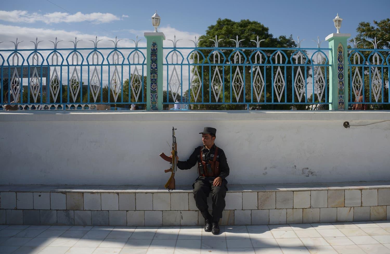 An Afghan policeman keeps watch as residents offer Eidul Fitr prayers in Mazar-i-Sharif. — AFP