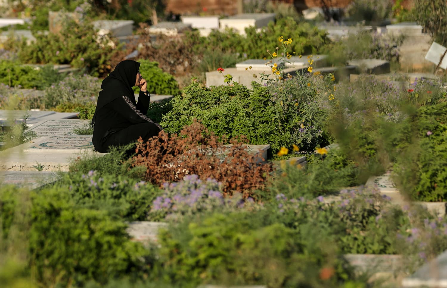 A Palestinian woman pray at a cemetery on the grave of a relative during the first day of Eidul Fitr, at the Israel-Gaza border east of Gaza city. — AFP