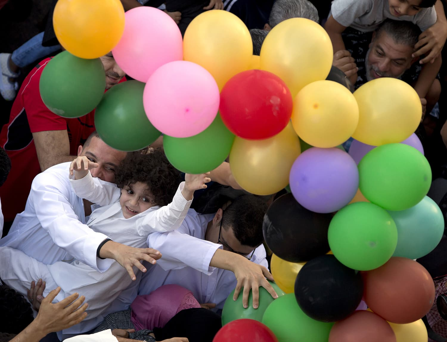 Muslims try to catch balloons distributed for free after Eid prayers outside al-Seddik mosque in Cairo, Egypt. — AP