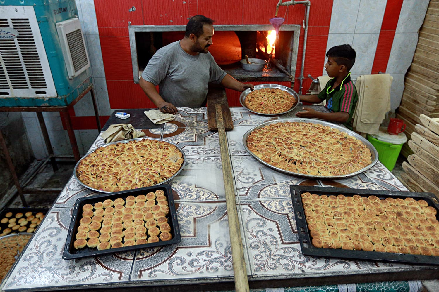 A baker cooks cookies in preparation for celebrations for Eidul Fitr in Baghdad, Iraq on June 14. — AP