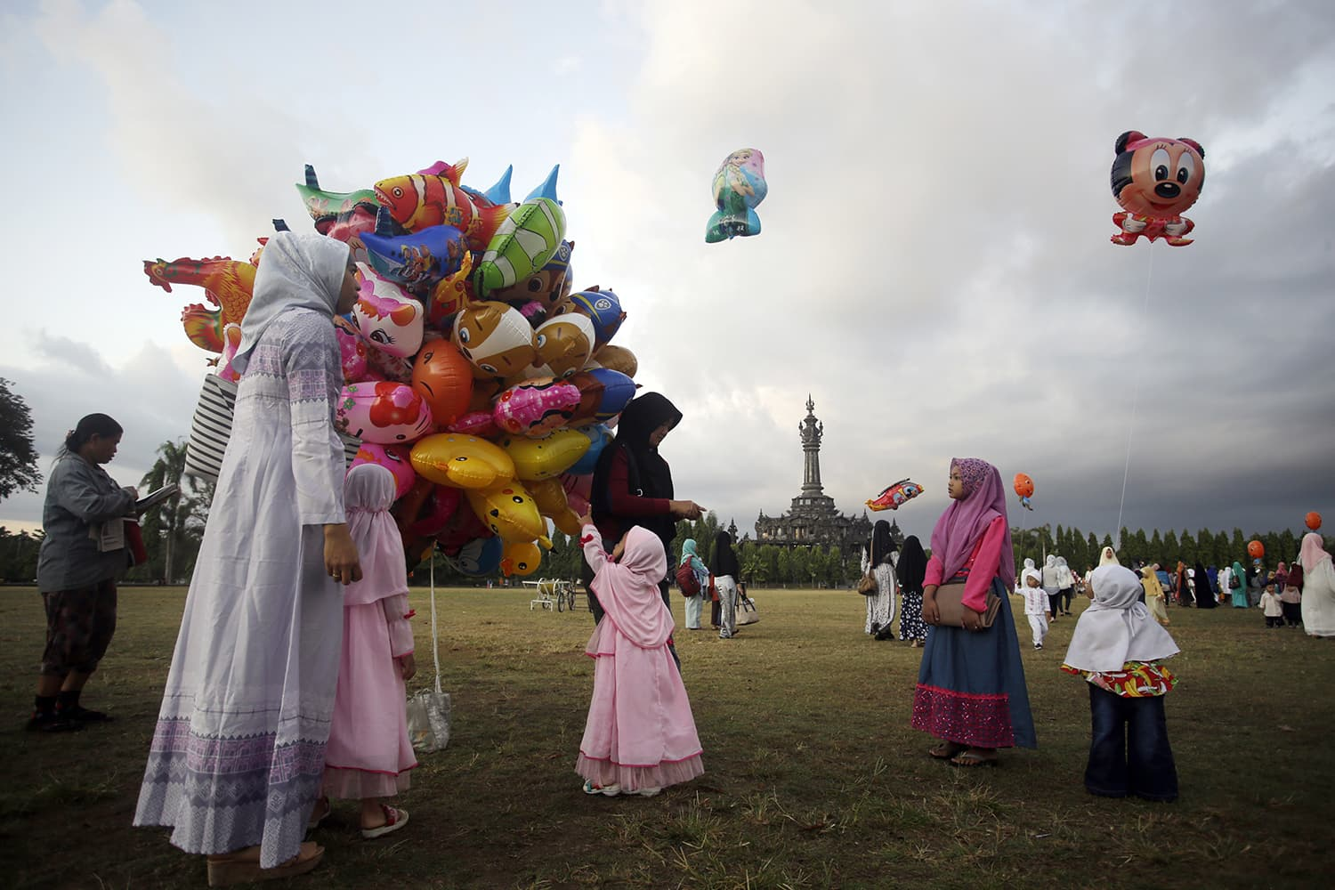 Children get balloons as they attend Eid prayers in Bali, Indonesia. — AP