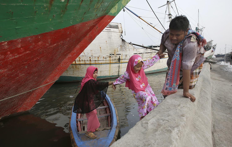 Indonesian Muslims arrive on boat for Eidul Fitr prayers at Sunda Kelapa port in Jakarta, Indonesia. — AP