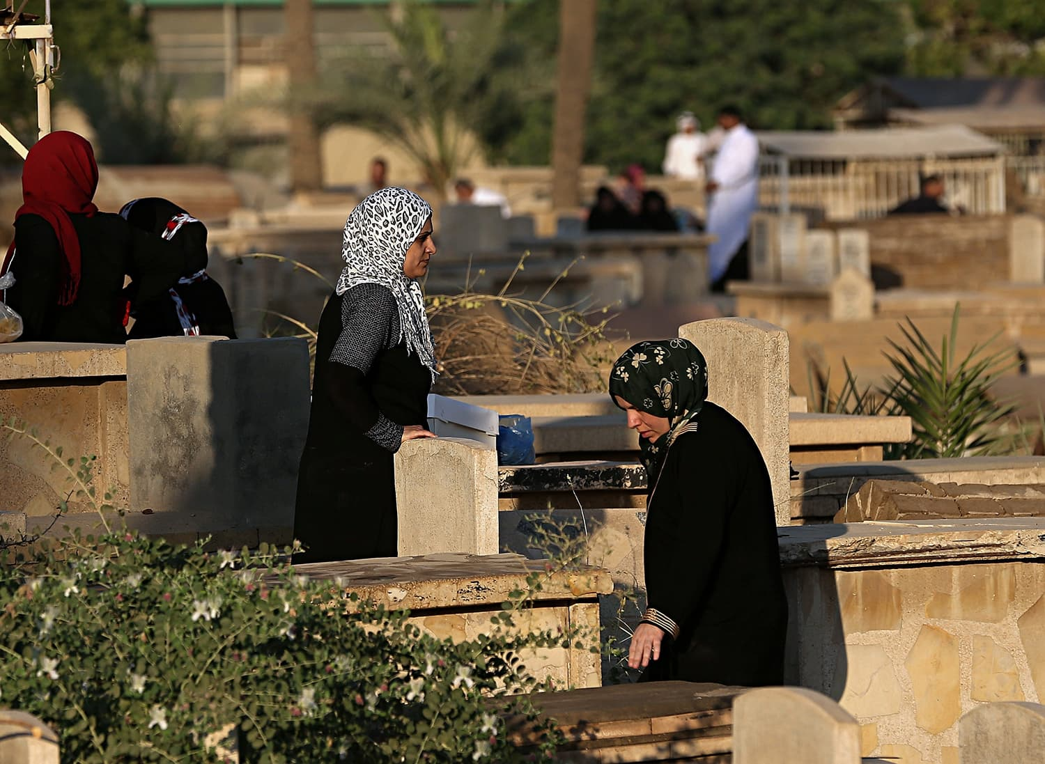 Iraqis visit the graves of relatives on the first day of Eidul Fitr at Ghazali cemetery in Baghdad, Iraq. — AP