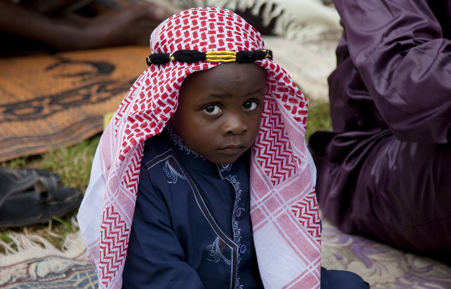 A Kenyan Muslim child listens to the Imam as he delivers sermon during the Eid prayers in Nairobi, Kenya. — AP