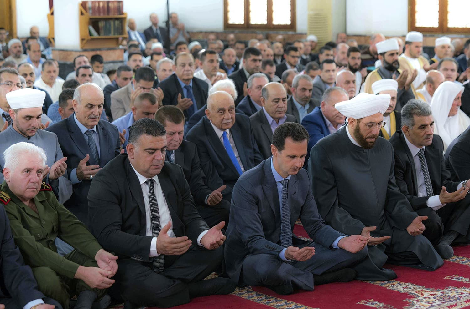 This photo released by the Syrian official news agency *SANA* shows Syrian President Bashar Assad, front third left, prays on the first day of Eidul Fitr in Tartous, Syria. — AP