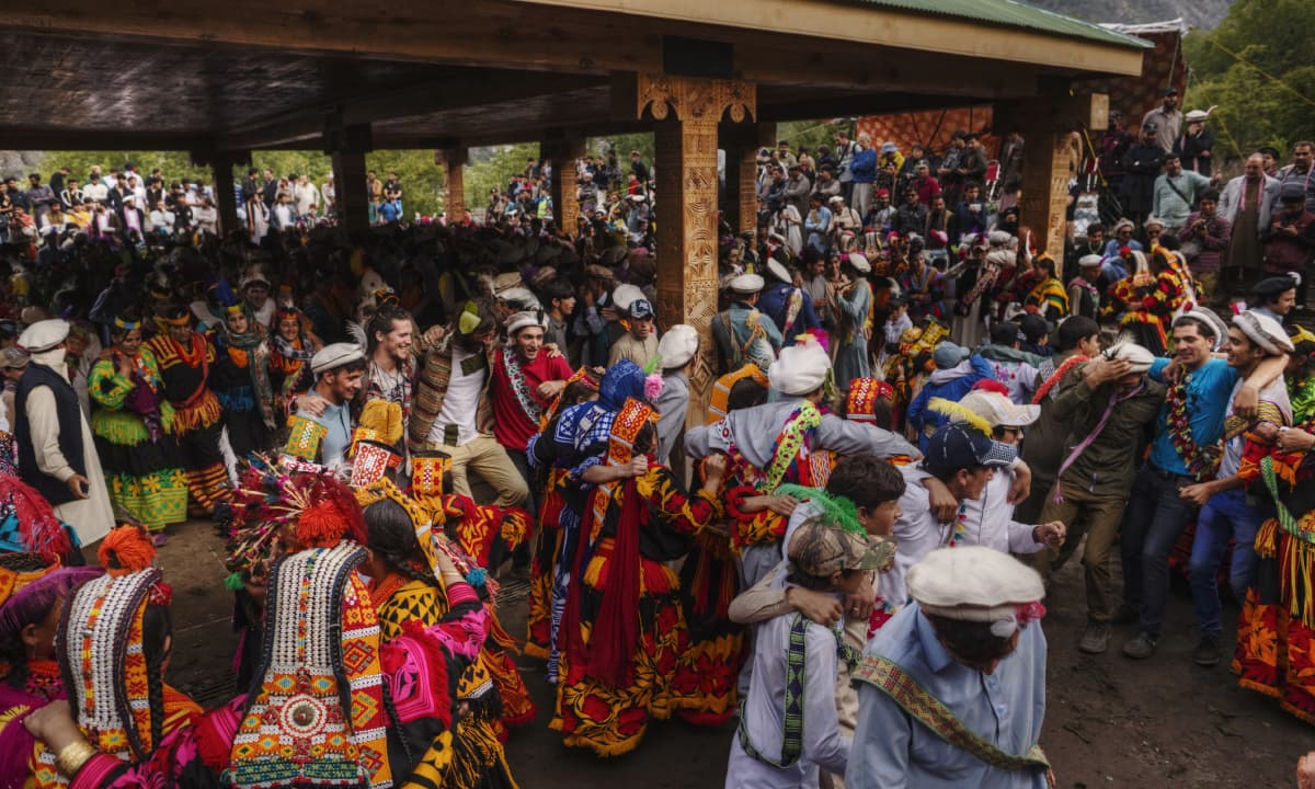 People dance, arm in arm, as spectators watch