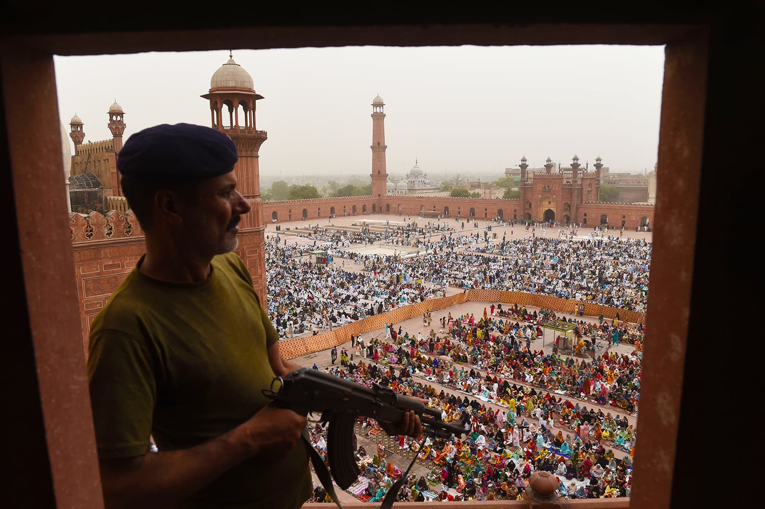 A policeman stands guard as worshippers pray to mark Eidul Fitr at the Badshahi Mosque in Lahore. — AFP