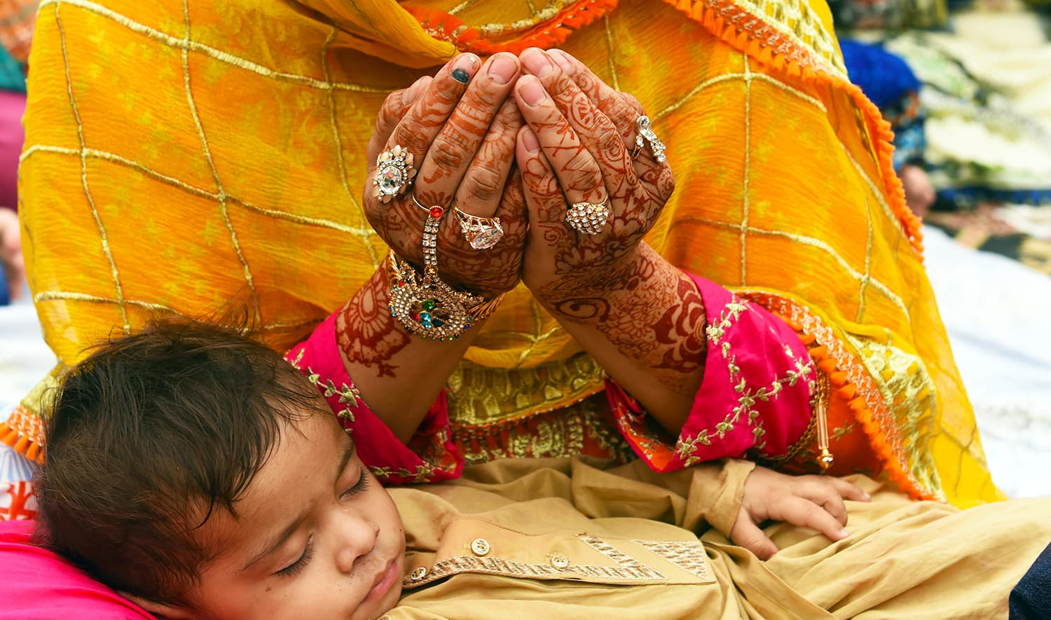 A woman holds her child as she prays to mark Eidul Fitr at the Badshahi Mosque in Lahore. — AFP