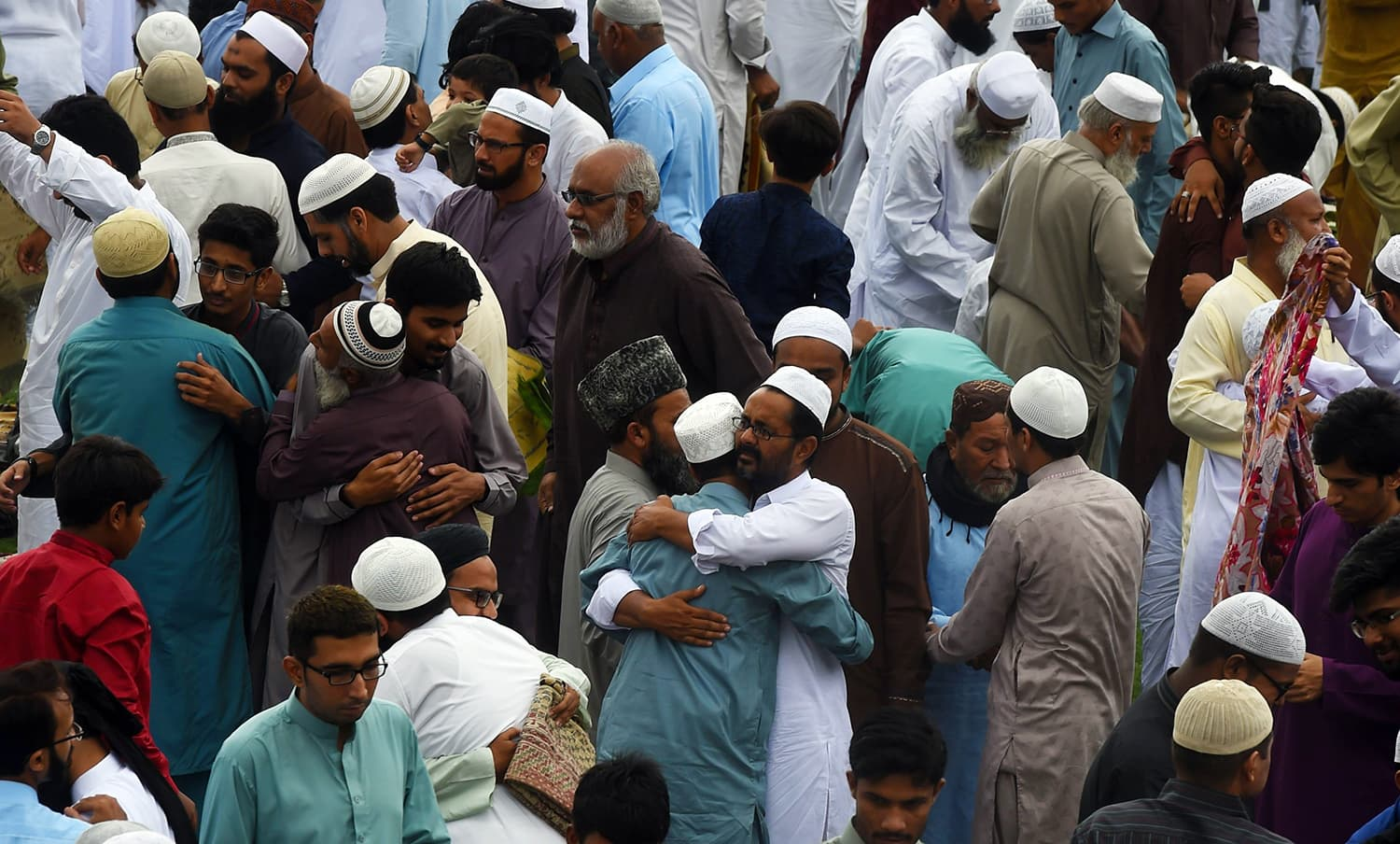 People exchange Eid greetings after offering Eidul Fitr prayers at an Eidgah ground in Karachi. — AFP