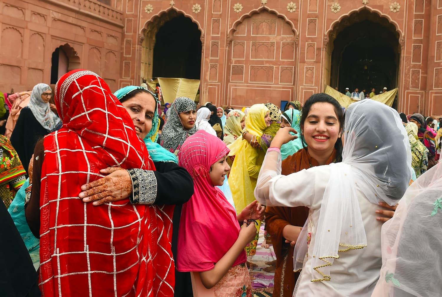 Women exchange Eid greetings after offering Eidul Fitr prayers at the Badshahi Mosque in Lahore. — AFP