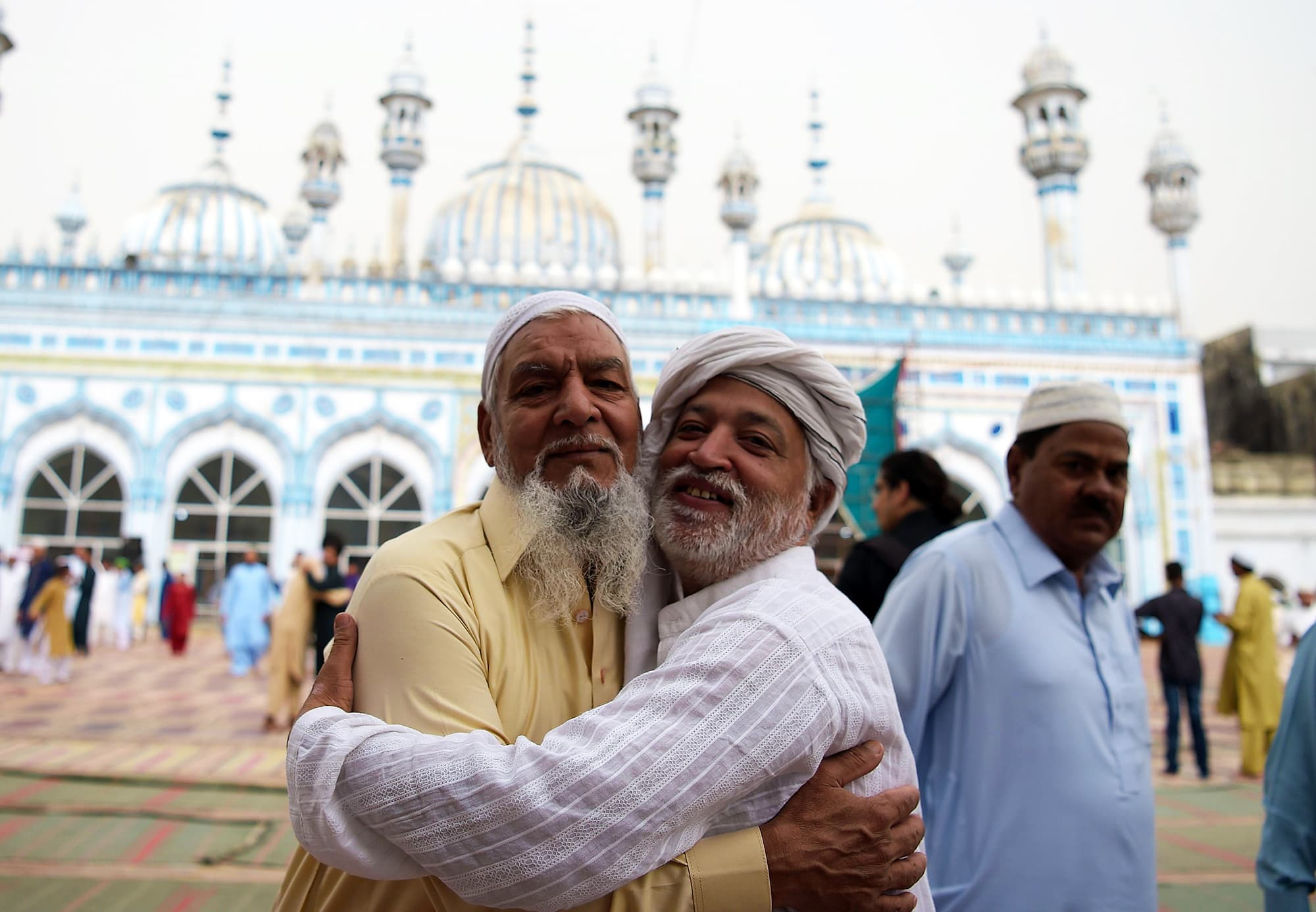 Pakistan Muslims exchange Eid greetings after offering Eid al-Fitr prayers at the at the Jamia Mosque in Rawalpindi. — AFP