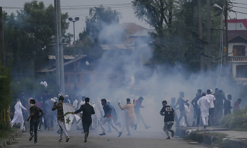 Kashmiri protesters run for cover amid tear gas smoke during a protest after Eid prayers in Srinagar. — AP