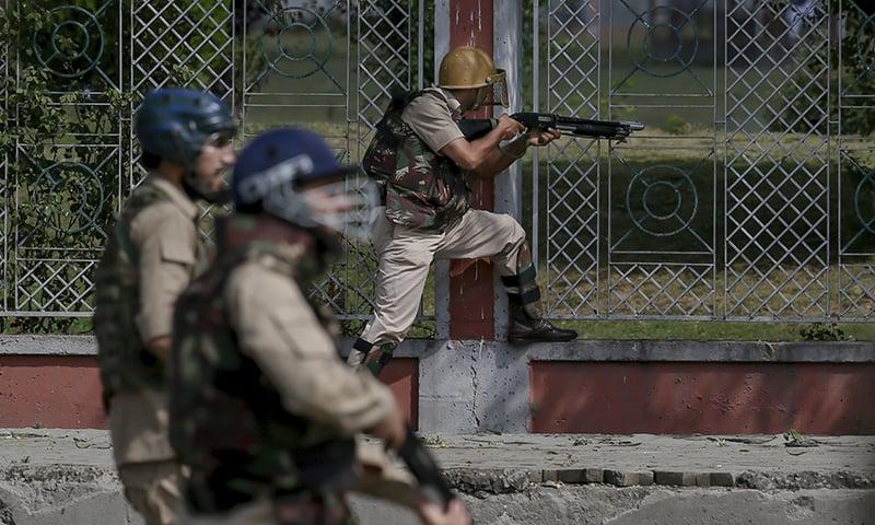 An Indian policeman fires a pellet gun at Kashmiri protesters after Eid prayers. — AP