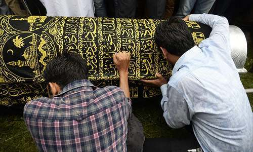 Relatives of slain editor Shujaat Bukhari mourn over the coffin during his funeral procession. — AFP