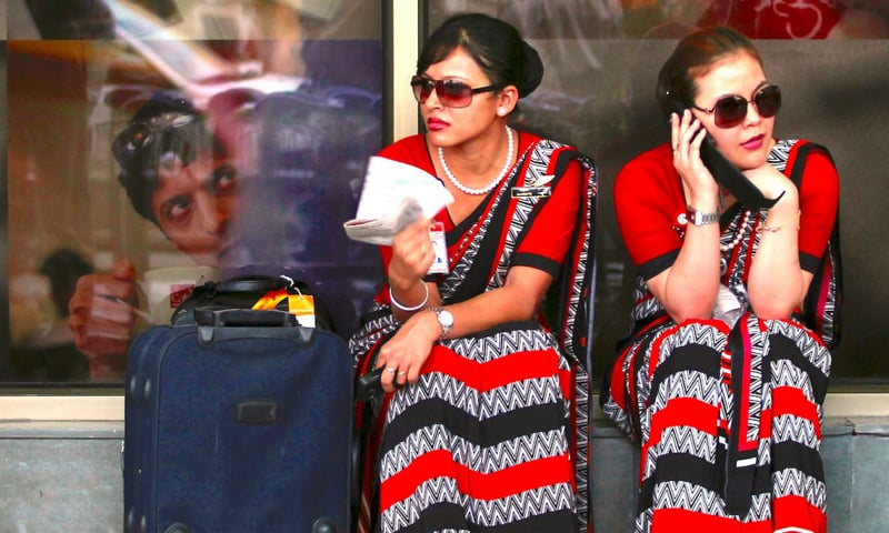 Air India air hostesses sit outside the domestic airport in New Delhi.—Reuters file photo