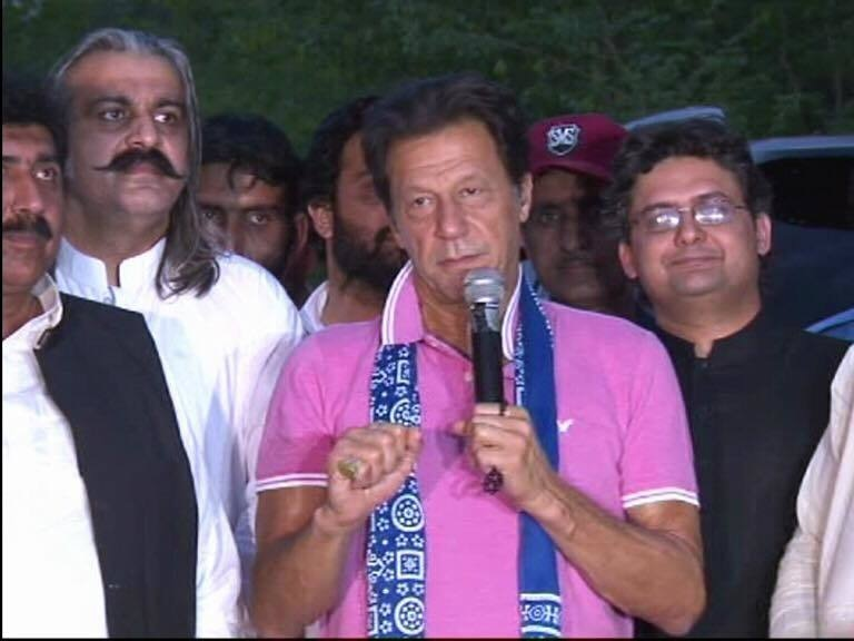 PTI chairman Imran Khan talks to party workers.