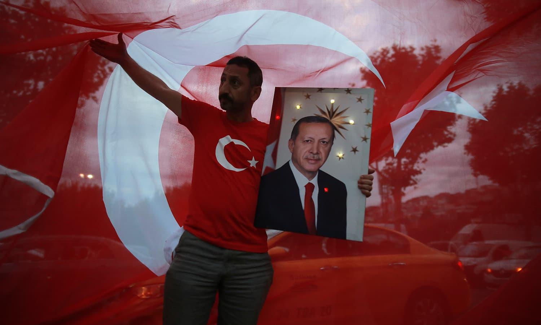صدر اردوان کے حامیوں نے ان کی تصاویر اٹھا کر نتائج مکمل ہونے سے قبل ہی جشن منانا شروع کردیا—فوٹو: اے پی