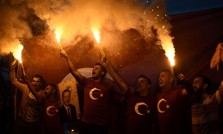 صدر اردوان کے حامیوں نے ان کی تصاویر اٹھا کر نتائج مکمل ہونے سے قبل ہی جشن منانا شروع کردیا—فوٹو: اے ایف پی