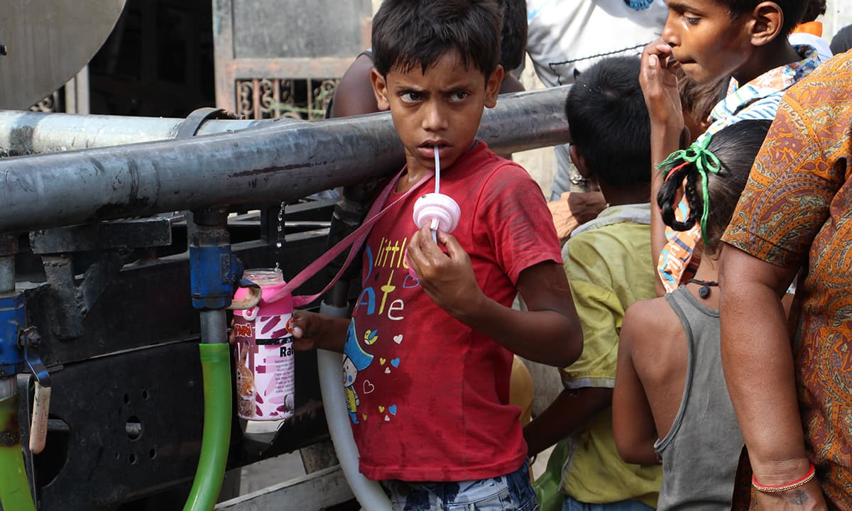 Children take water from a tanker in Wazirpur | Aabid Shafi