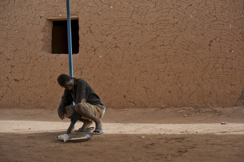 A young migrant who has been expelled from Algeria sits in a transit center in Arlit, Niger on June 1. Traumatized by his experience, he has not spoken and is helped by other migrants for food and bathing. His case puzzles aid workers who cannot find out where he is from in order to repatriate him. — AP