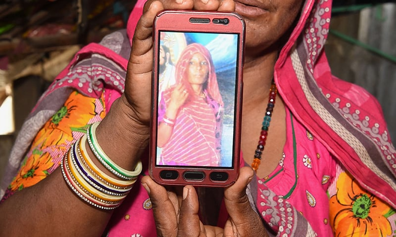 Mohinidevi Nath displays a photo on a mobile phone of her cousin Shantadevi Nath, who was killed by a mob that falsely believed she was intent on abducting children. —AFP