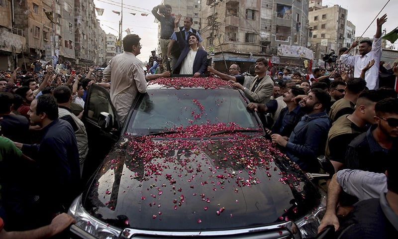 Bilawal Bhutto-Zardari waves to supporters during the rally in Lyari. — AP