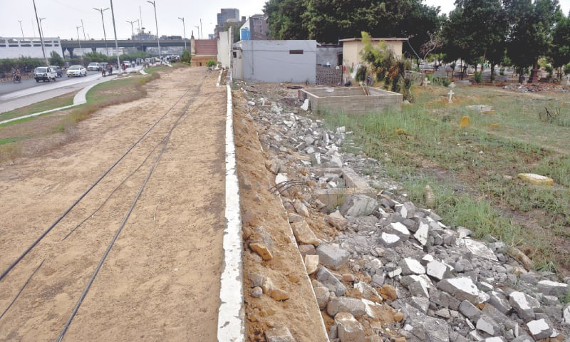 THE Gora Qabristan wall along the green belt on Sharae Faisal, knocked down without a thought by workers of Cantonment Board Faisal in a bid to do away with advertisement walls.—Photo by Fahim Siddiqi / White Star