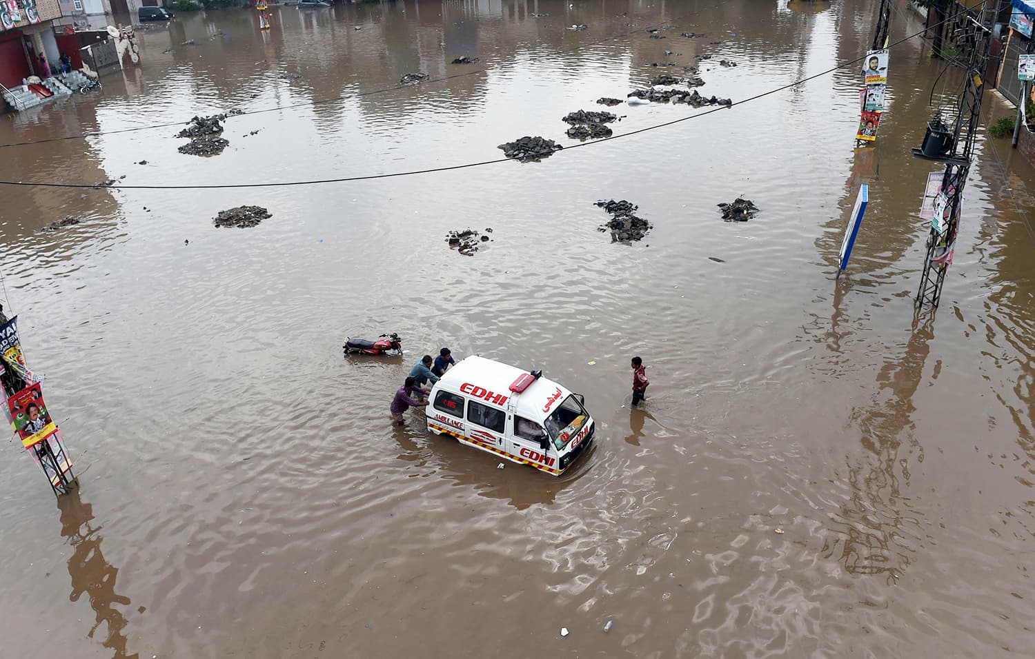 Men push an ambulance through a flooded square AFP