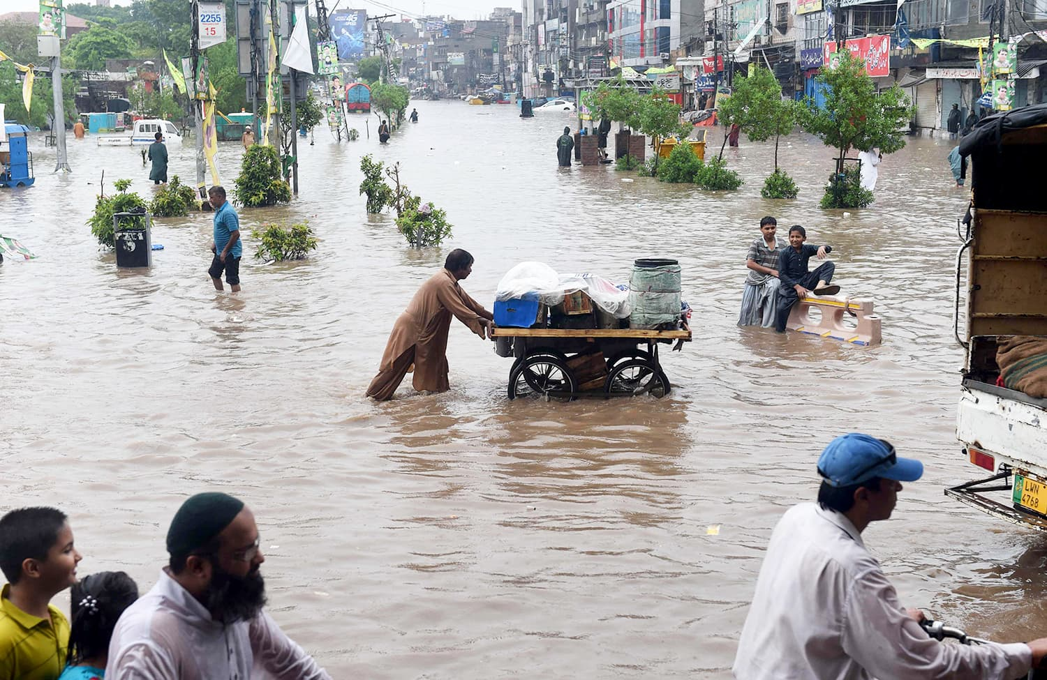 Commuters cross a flooded street after heavy rains in Lahore AFP