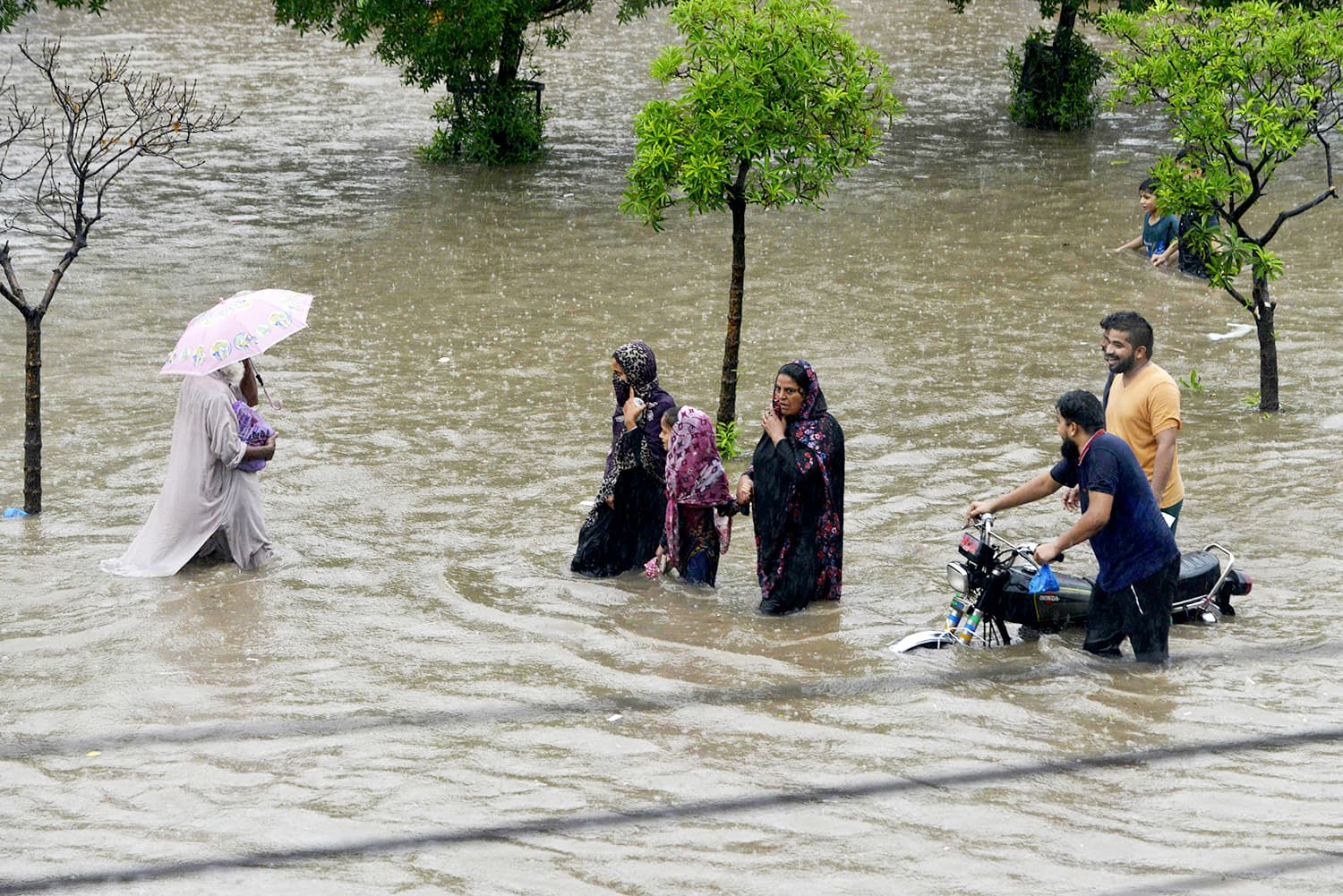 Lahore residents wade carefully through a flooded street AFP