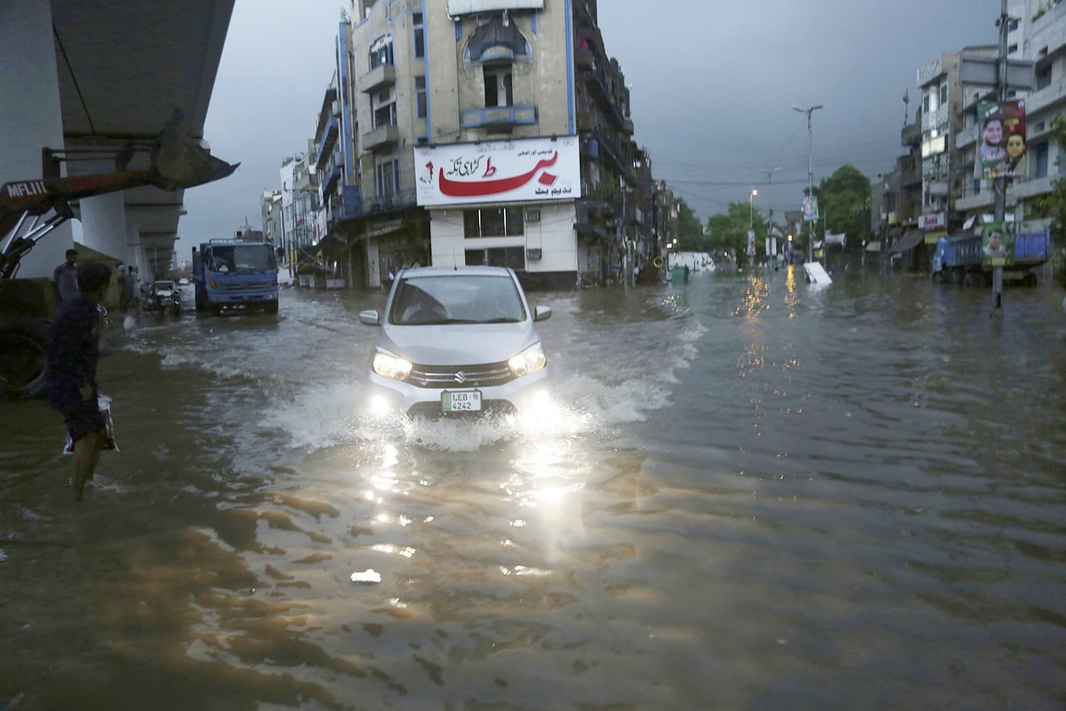 People travel through a road still flooded in the evening after heavy rainfall in the early morning hours AP
