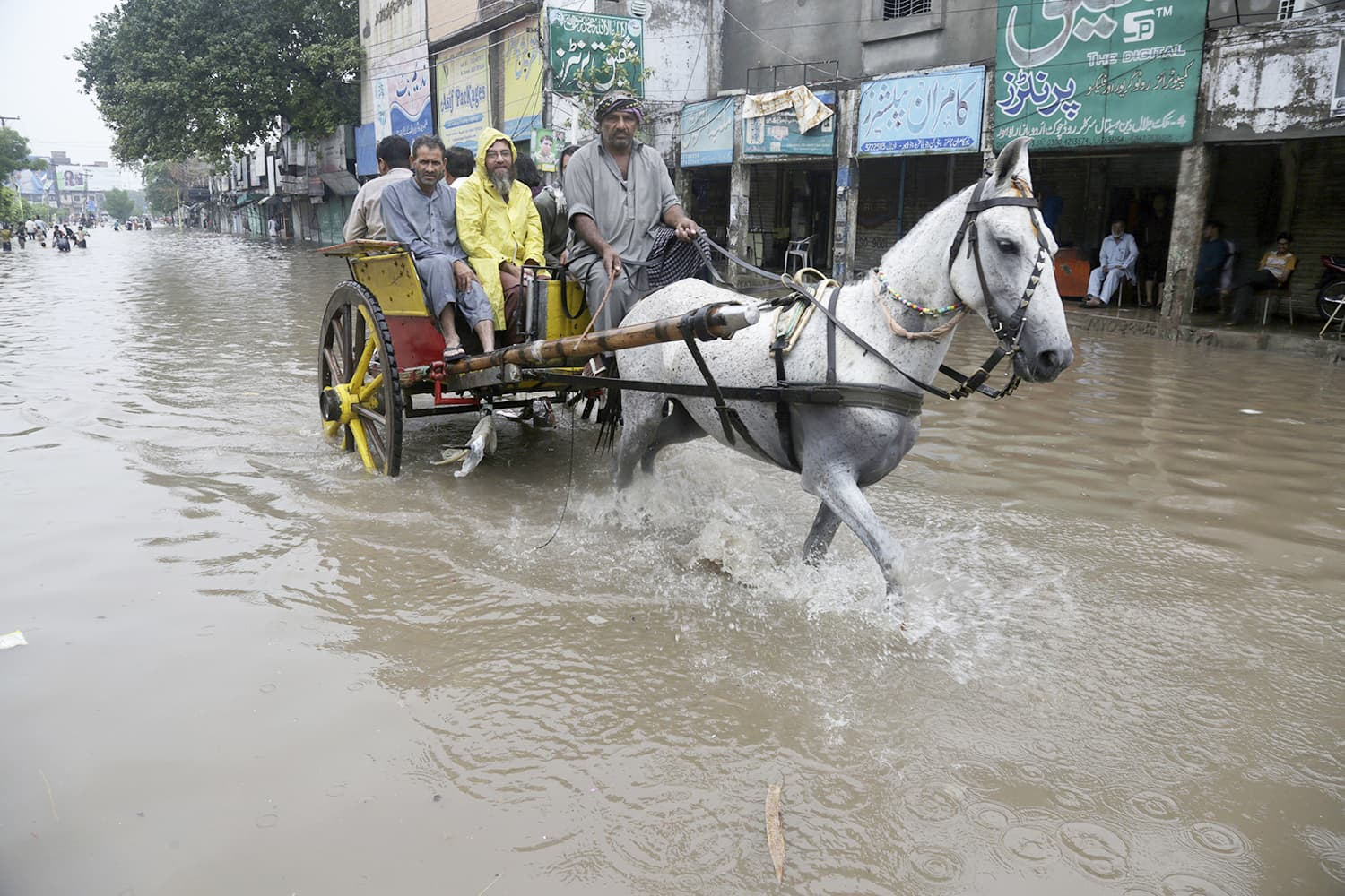 A horse-cart owner carries people through a heavily-flooded street AP