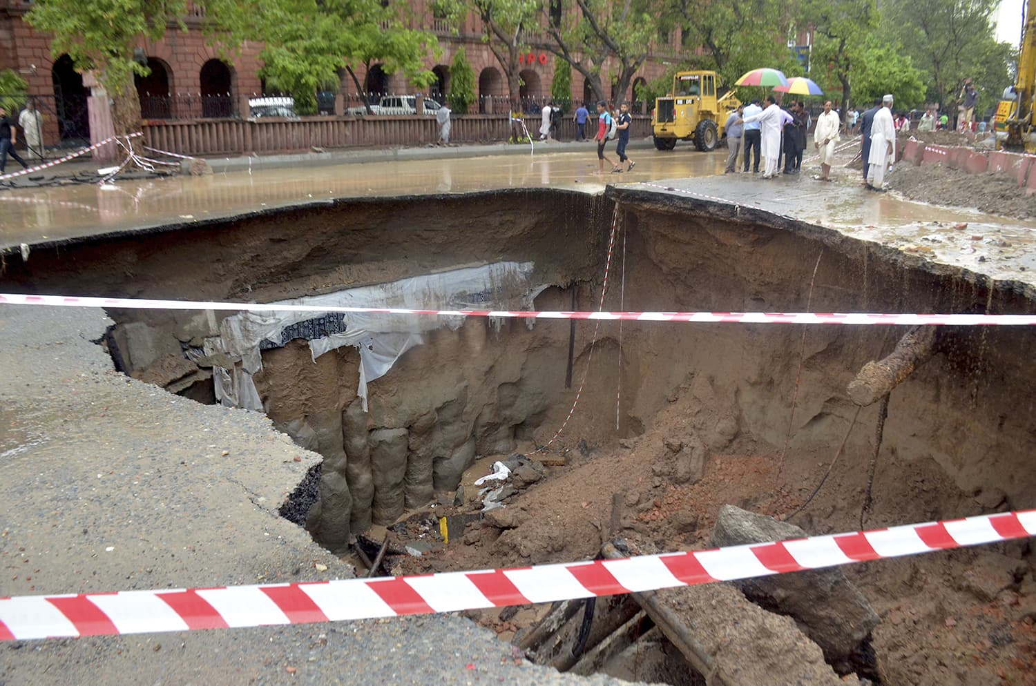 Residents look at a road caved in due to the heavy rain fall AP