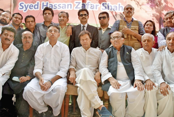 Chairman Imran Khan and Zafar Ali Shah on stage with other PTI leaders including Asad Umar and Ghulam Sarwar. — White Star