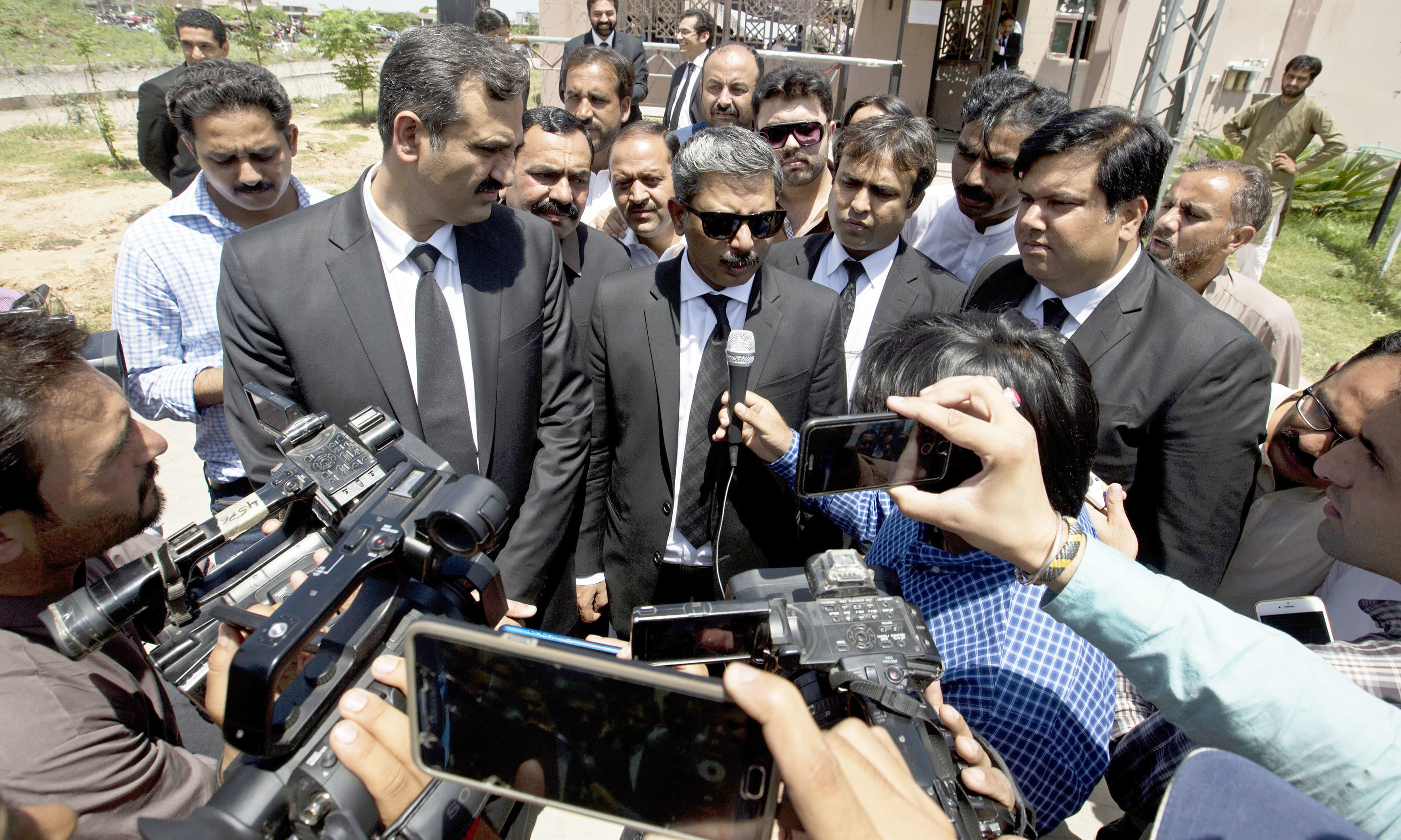 The counsel for Nawaz Sharif briefs journalists outside the court. — AP