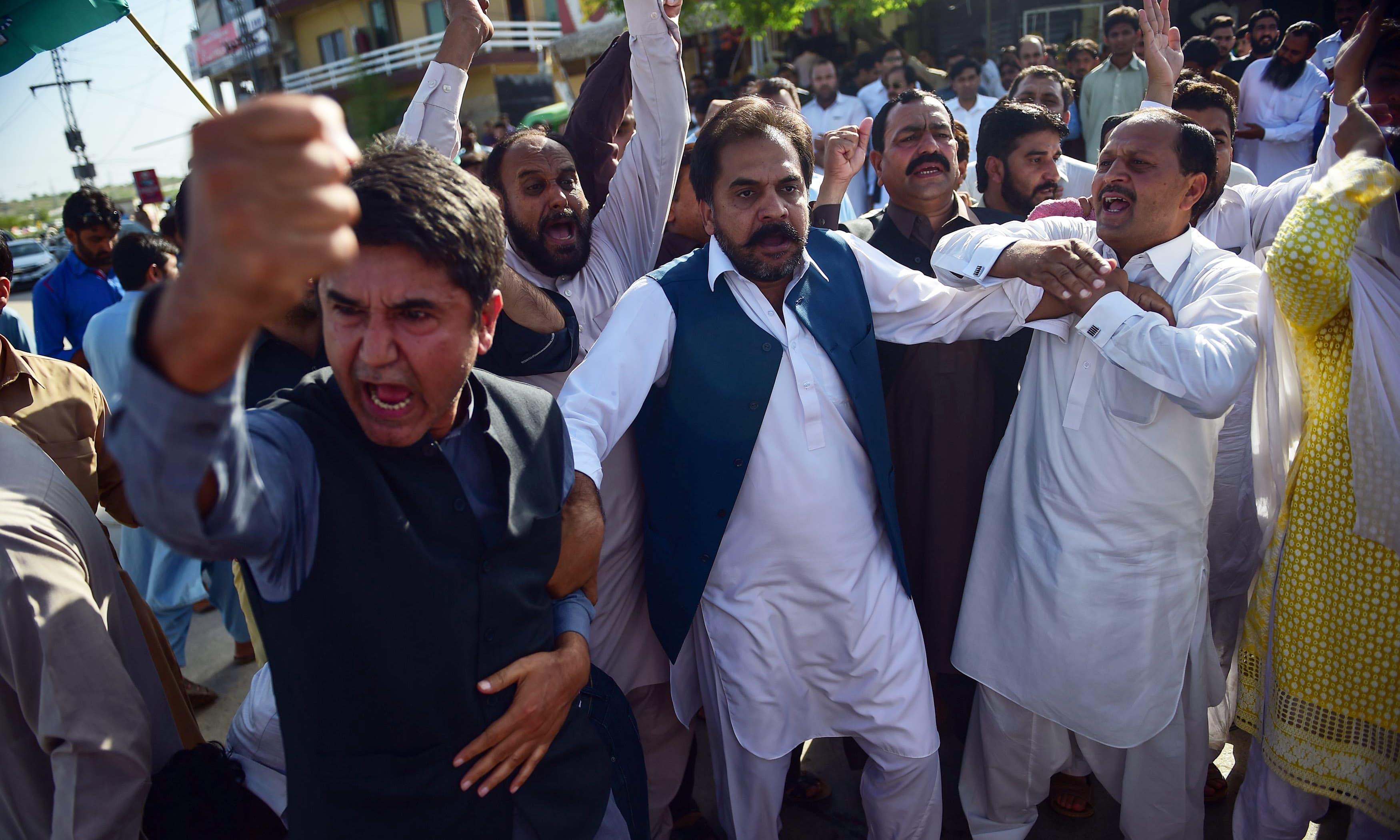 PML-N activists shout slogans outside court after the sentencing of former prime minister Nawaz Sharif in Islamabad. —AFP