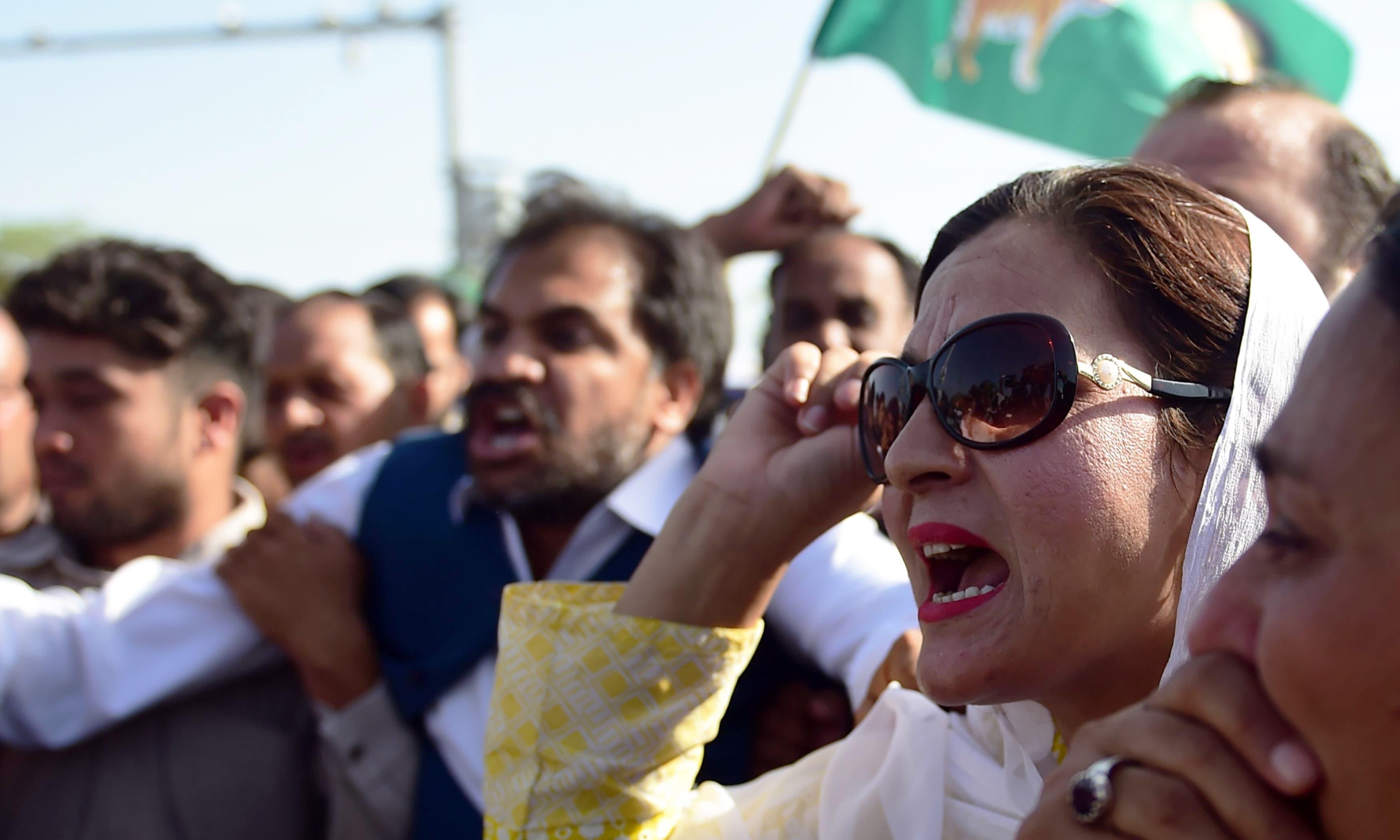 PML-N activists shout slogans outside court after the sentencing of former prime minister Nawaz Sharif in Islamabad.—AFP