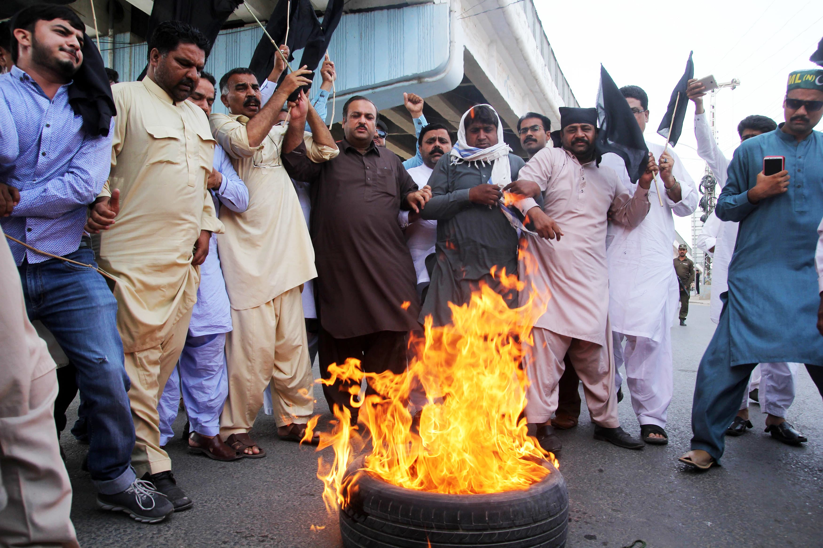 Activists of Pakistan Muslim League-Nawaz (PML-N) burn tyres after the sentencing decision against former prime minister Nawaz Sharif, during a protest in Multan on July 6, 2018.  Pakistan's former prime minister Nawaz Sharif was sentenced in absentia to 10 years in prison by a corruption court in Islamabad on July 6, lawyers said, dealing a serious blow to his party's troubled campaign ahead of July 25 elections.  / AFP PHOTO / SS MIRZA — AFP or licensors