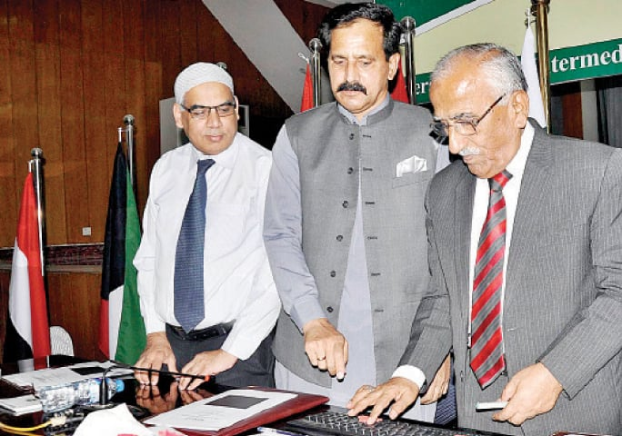 Caretaker Minister for Federal Education and Professional Training Mohammad Yusuf Sheikh pushes a button on the computer while declaring the SSC annual examination results at the FBISE Office on Friday. — APP
