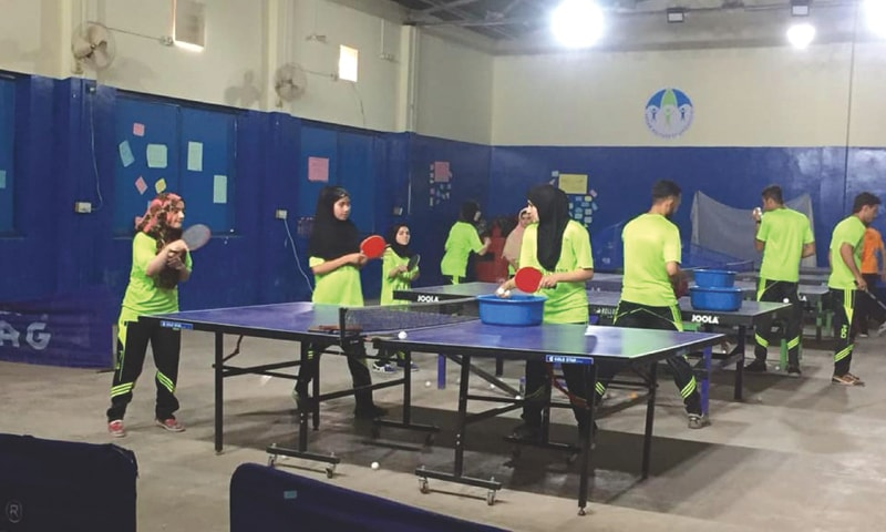 Helping schoolgirls play table tennis at the Absar Welfare Foundation