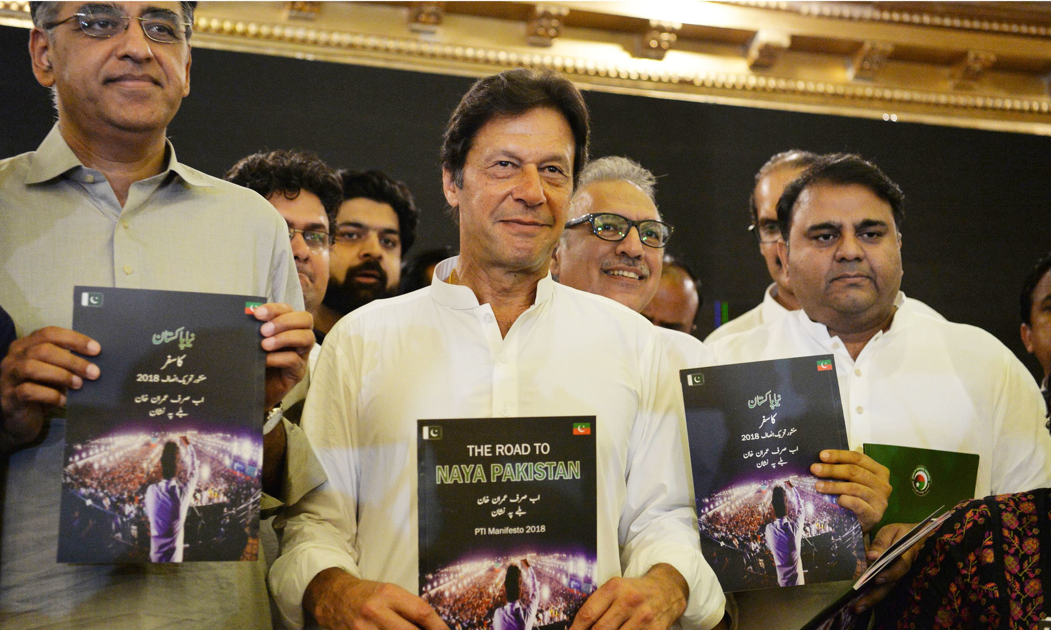 PTI leaders display copies of their party's manifesto. —AFP