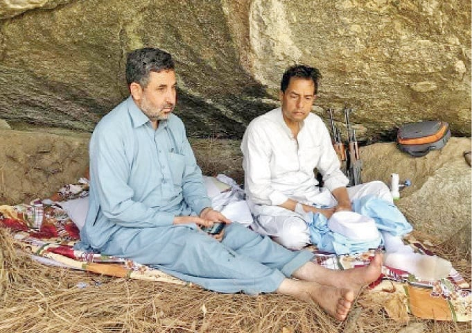 Mohammad Safdar is seen sitting in a cave in Tanawal area before proceeding to Rawalpindi. — Dawn