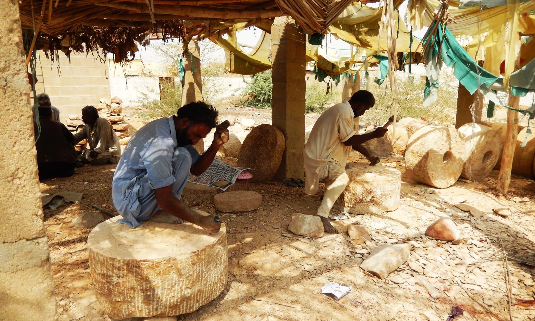 چھپر کے نیچے چند سنگتراش ہتھوڑی اور تیشوں سے پتھروں کو کاٹ رہے ہیں—تصویر ابوبکر شیخ